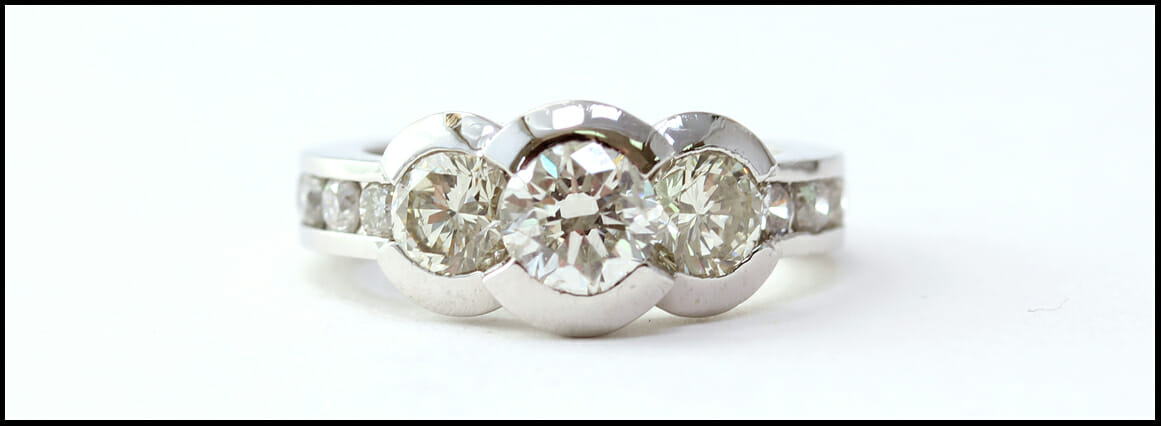 Diamond Remount ring with three central round diamonds in half bezels, diamond channel band, in platinum